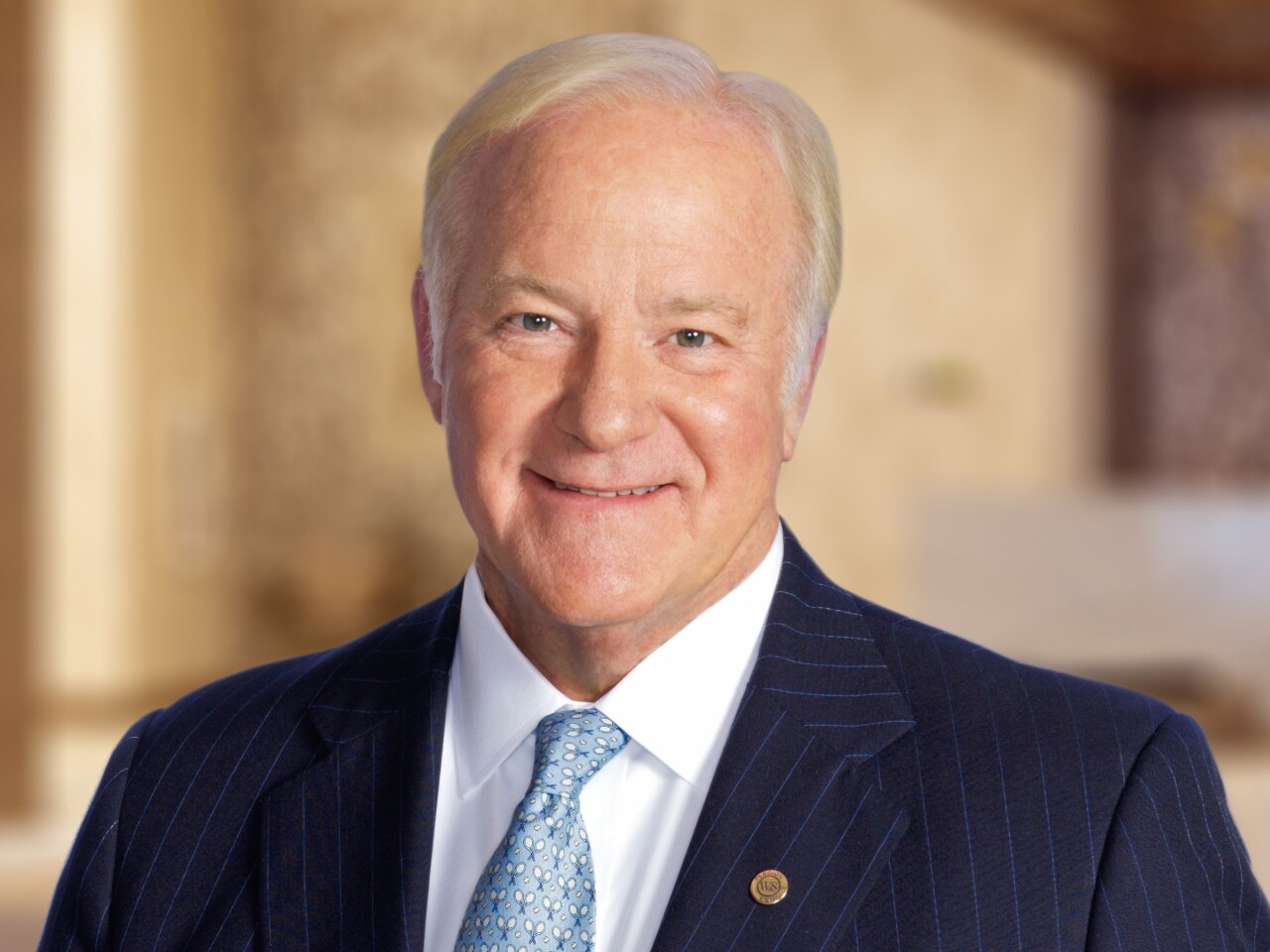 Western & Southern Financial Group CEO John Barrett is smiling in this photo. He has short white hair and is wearing a pale blue patterned tie, a white shirt and a navy pinstripe suit jacket.