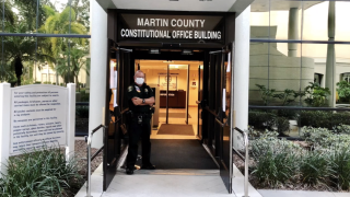 Deputy wearing mask stands at entrance to Martin County Constitutional Office Building