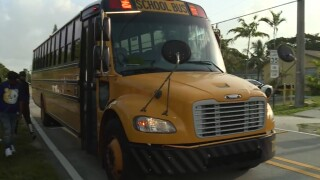 A Palm Beach County school bus picks up students in West Palm Beach on Aug. 25, 2021.jpg