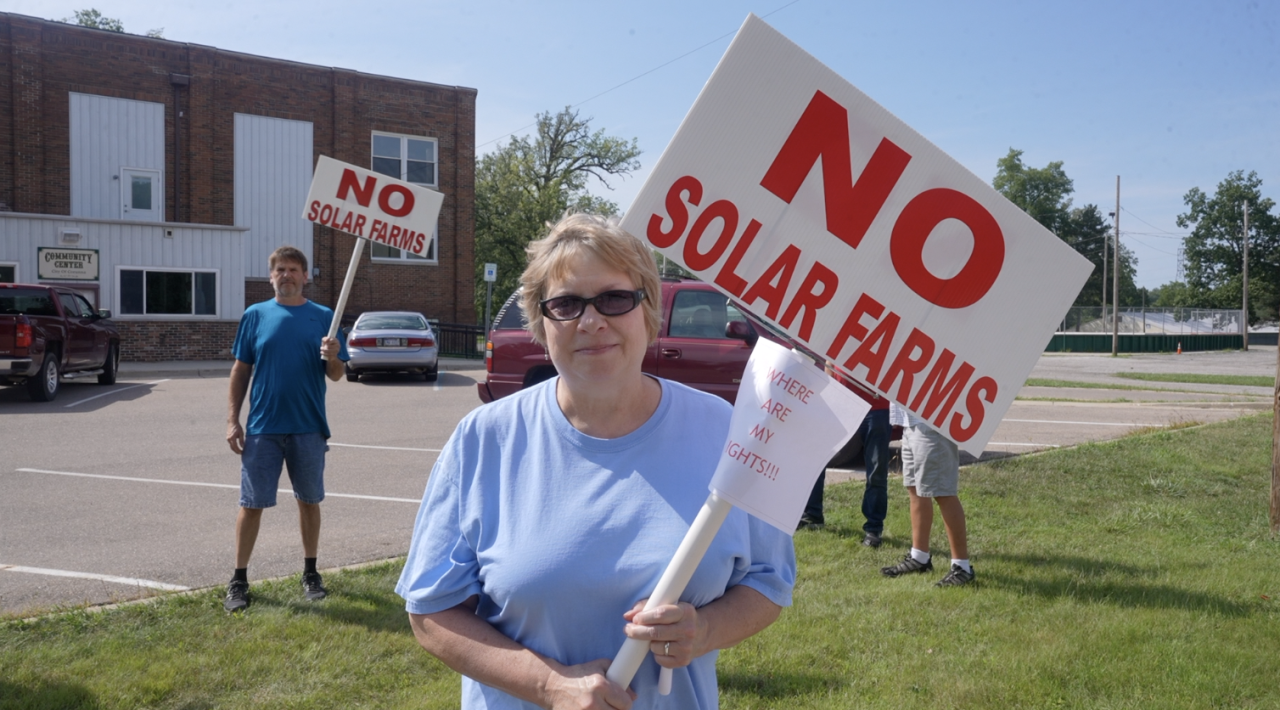 """Tammy Dasen with her """"NO SOLAR FARMS"""" sign"""