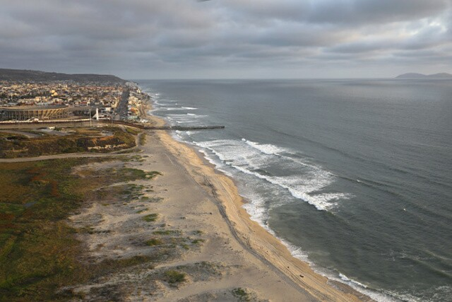 Aerial views of the U.S.-Mexico border fence at the beach