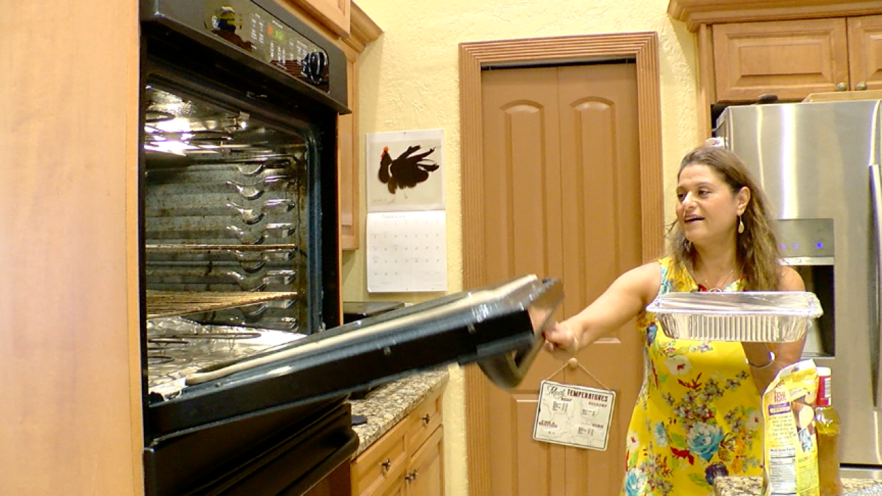 Woman with an aluminum tray wrapped in tin foil on the top holding an oven door open to put the tray in the oven.
