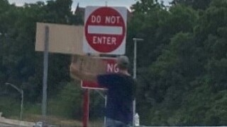 panhandler-holding-sign-standing-by-do-not-enter-sign.jpg