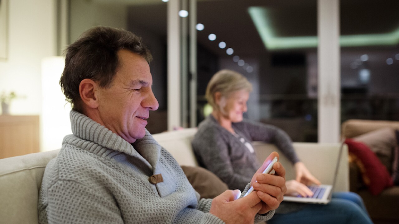 Senior couple with laptop and smartphone sitting on couch