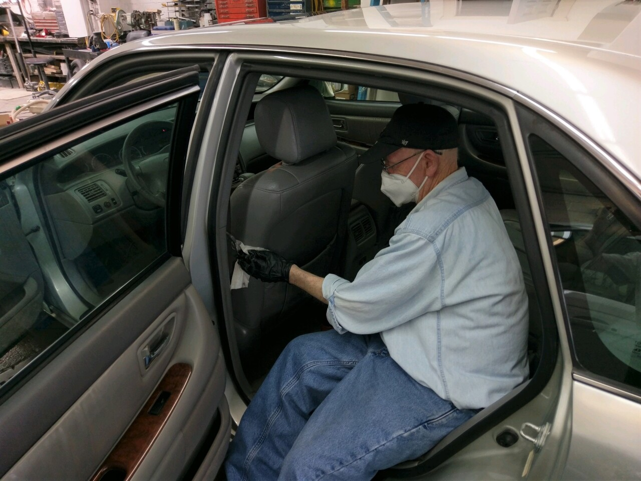 Volunteer Mike Truman helps clean a donated 2000 Toyota Avalon for Samaritan Car Care Clinic. Truman is wearing a mask and gloves while wiping down the driver's seat.