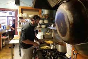 Eli Eller cooking at No Sweat Cafe