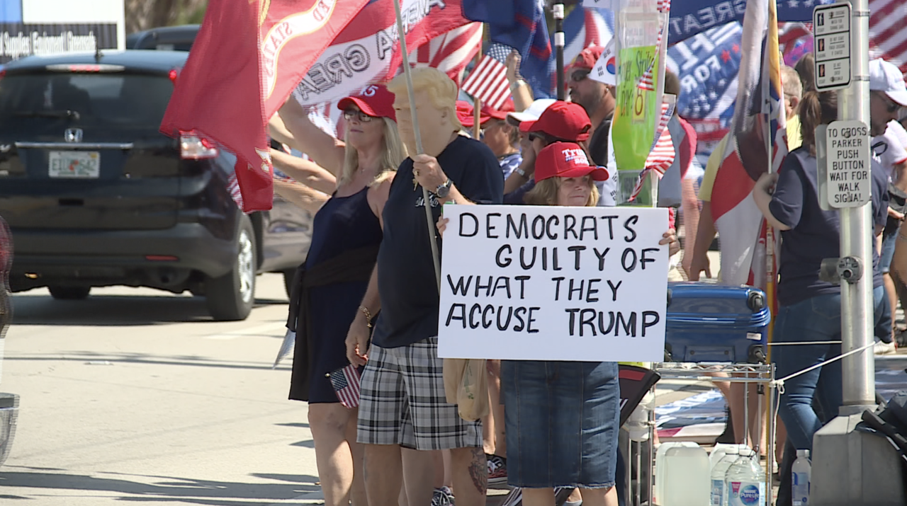 Woman holding sign 'Democrats guilty of what they accuse Trump' at rally, Feb. 15, 2021