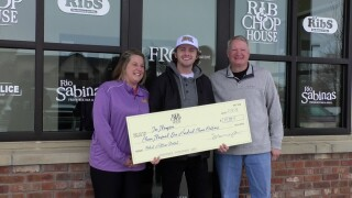 Rib and Chop House presents Joe Thompson with his winning check.
