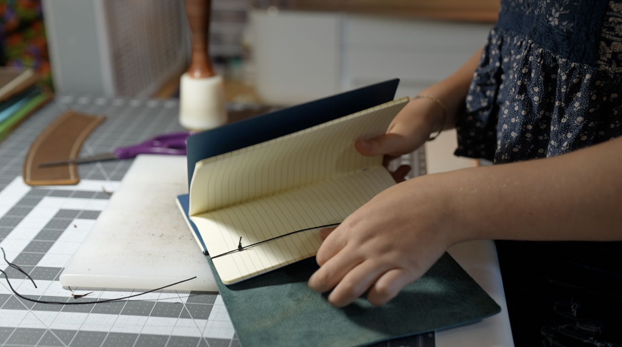 Evelyn putting two notebooks into the refillable leather journal