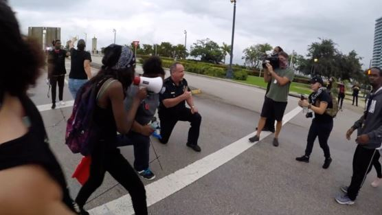 Deputy Chief Rick Morris kneels with protesters in West Palm Beach, June 2, 2020