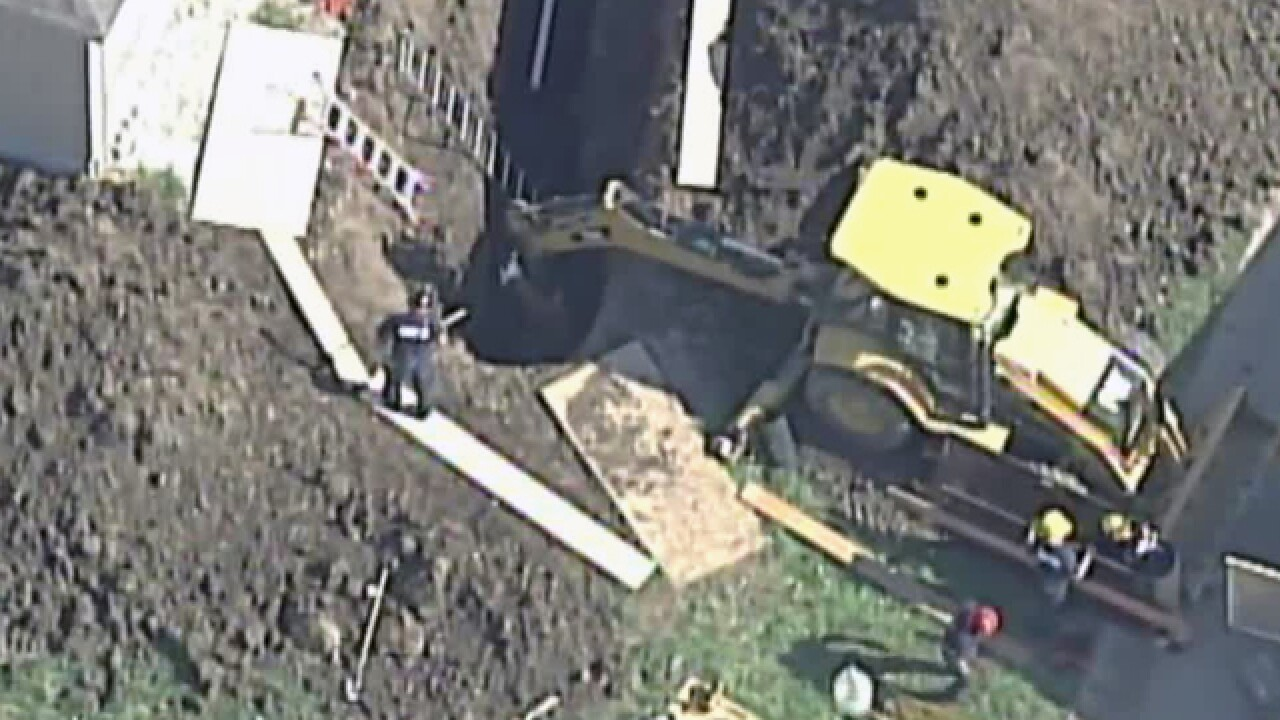 Crews work to rescue man from trench