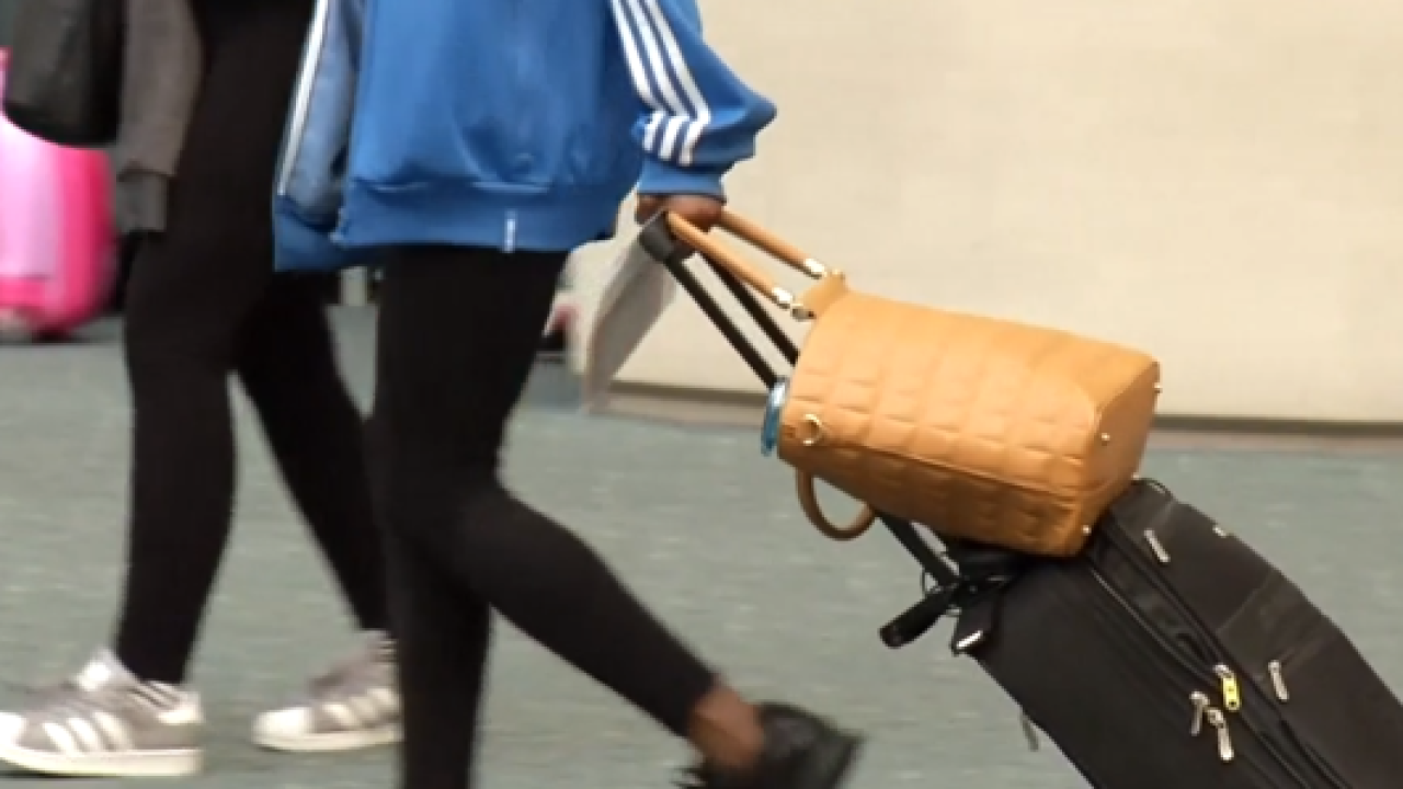 Woman toting tan and black luggage through airport