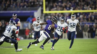 Baltimore Ravens QB Lamar Jackson runs past Tennessee Titans during playoff game