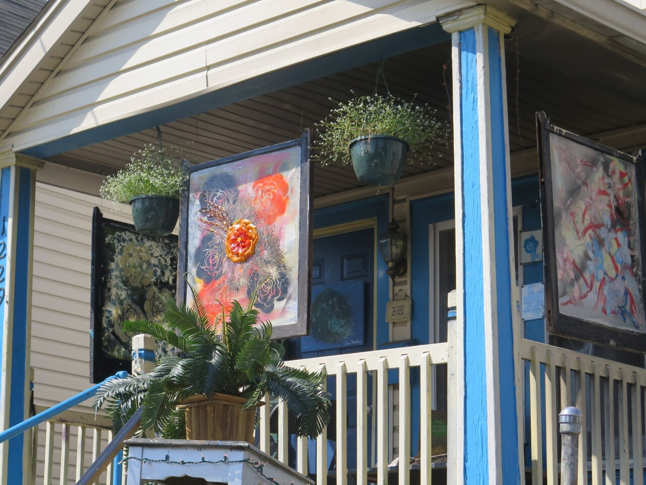 Nina Edwards has three windows hanging from the porch of her house in Covington. The most prominent window features flowers in blue and orange.