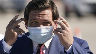 Gov. Ron DeSantis puts on mask at COVID-19 testing site at Hard Rock Stadium, Jan. 6, 2021