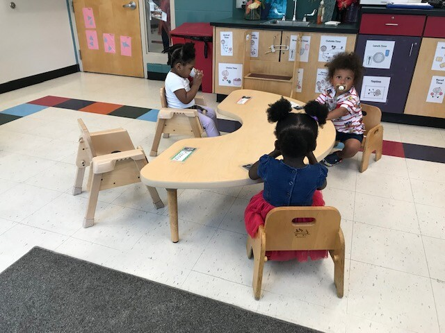 Students sitting at a table at a daycare in Milwaukee County