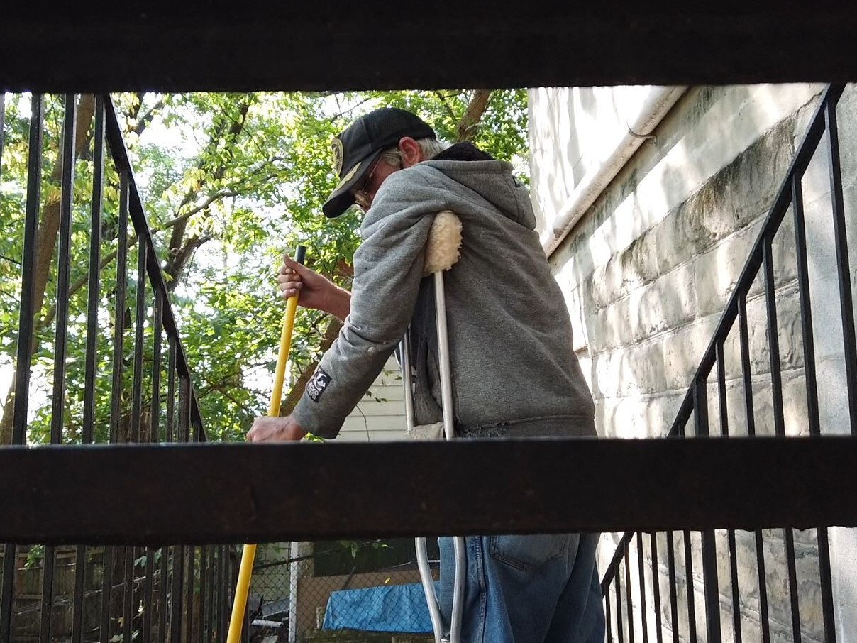 Terry Walls sweeping the back steps of the Joe Williams Family Center. The photo was taken from behind the staircase and shows Walls pictured between several steps.