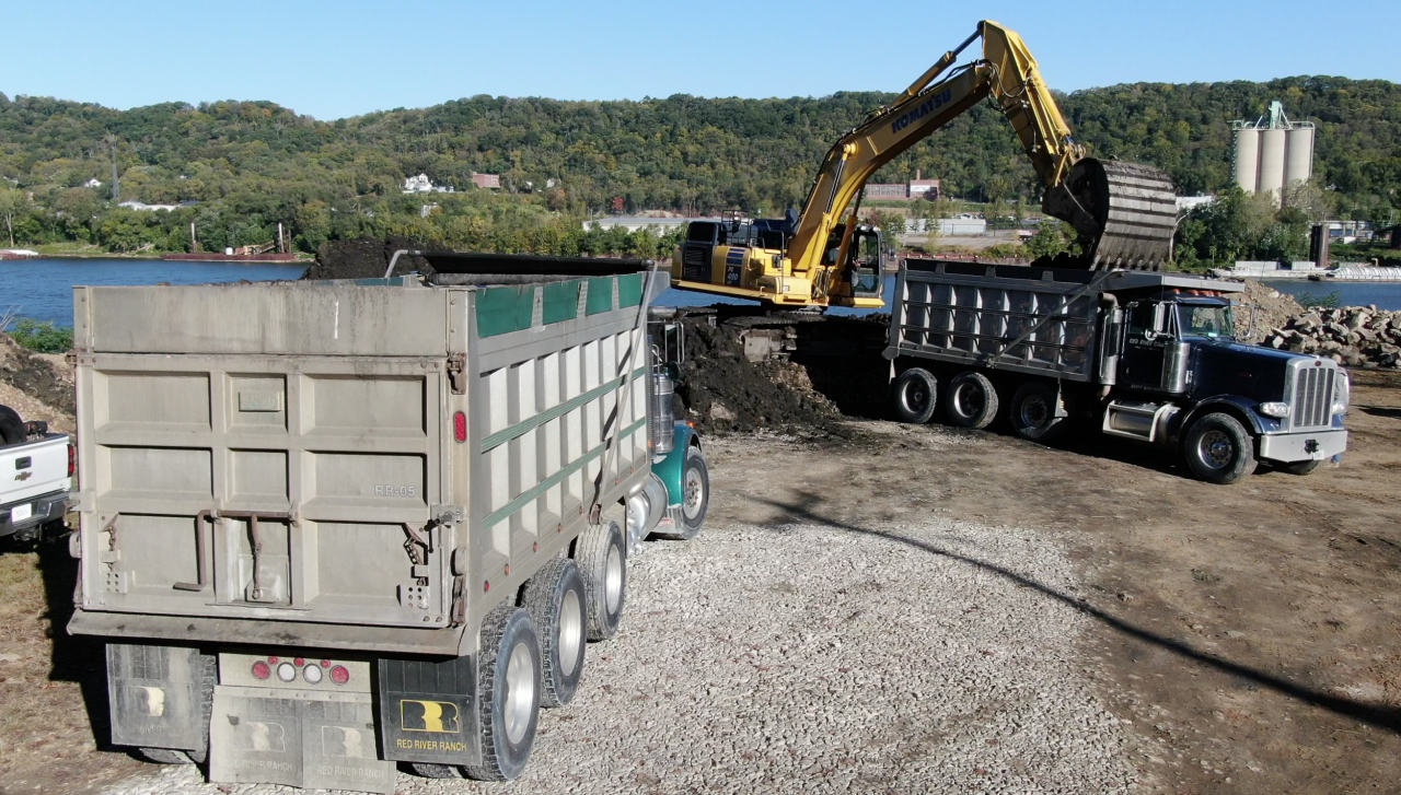 SKY 9 shows workers loading contaminated waste into dump trucks on the Bells' property