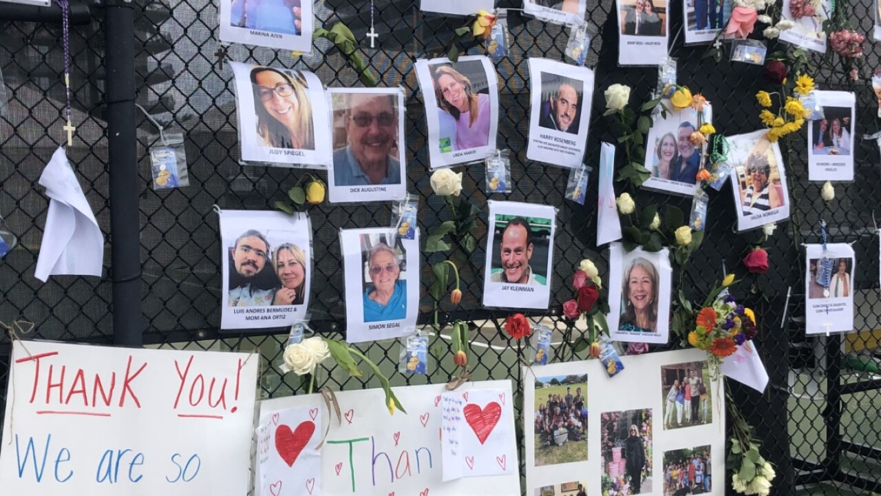 A wall shows photos of dozens of missing people from the Champlain Towers condo collapse on June 28, 2021.jpg