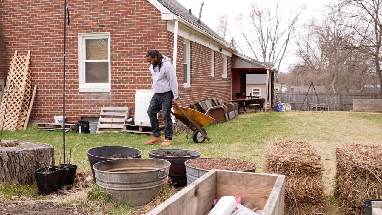 Allan Whitley walks a wheelbarrow through his backyard garden.