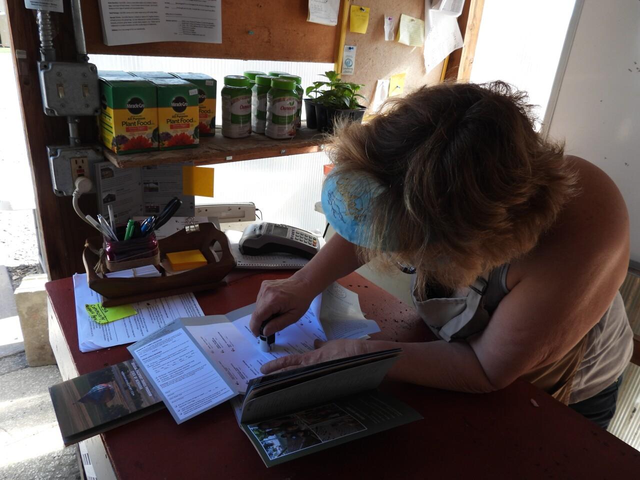 Barb Quinn stamps a passport at Wenninghoff Farm Market