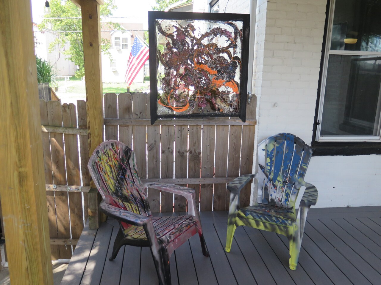 This photo shows the first window that Nina Edwards painted along with two Adirondack chairs she painted. The window and chairs are painted with abstract designs in bright colors.