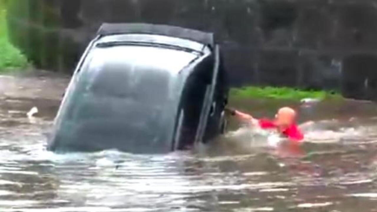 Louisiana firefighters jump into floodwaters to save woman trapped in car