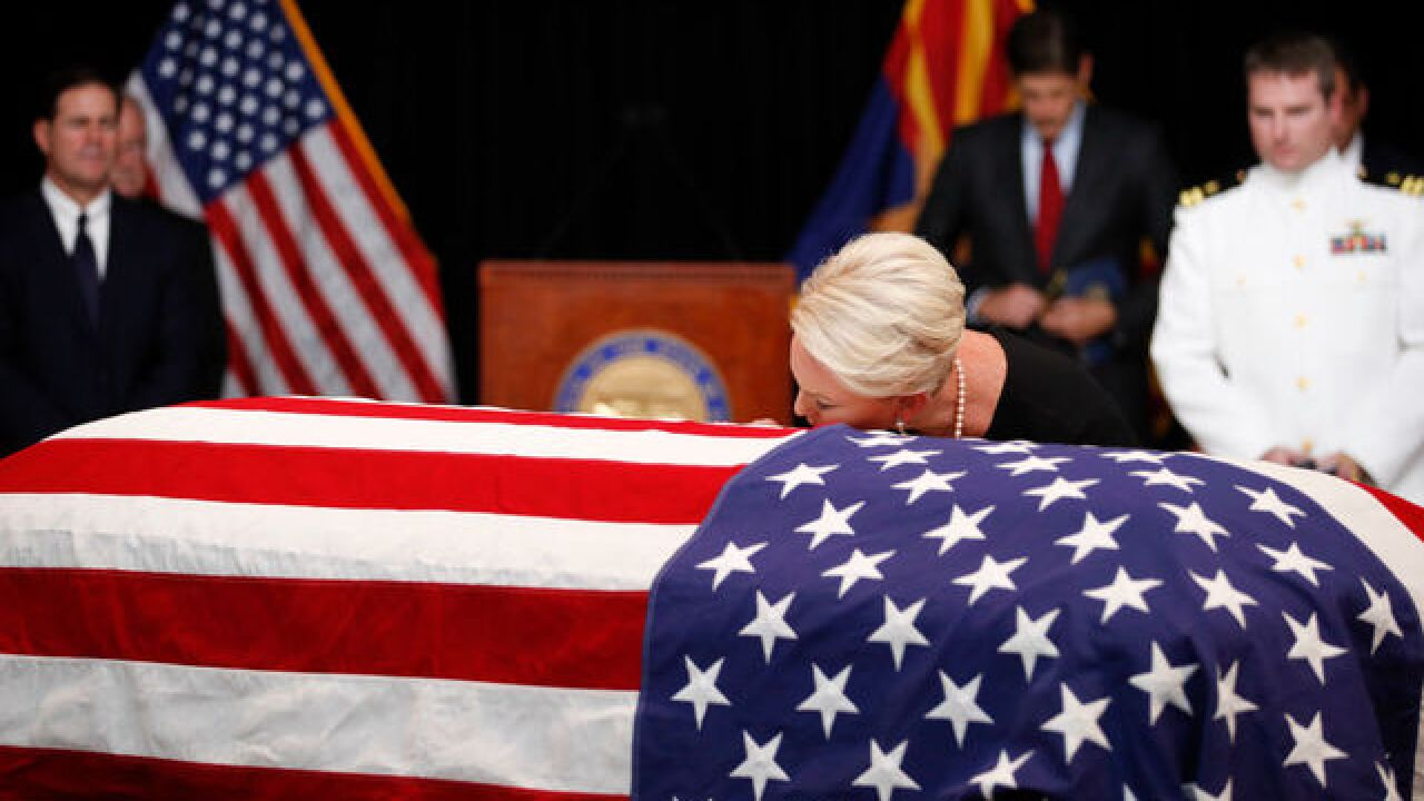 Cindy McCain kisses husband's casket at service