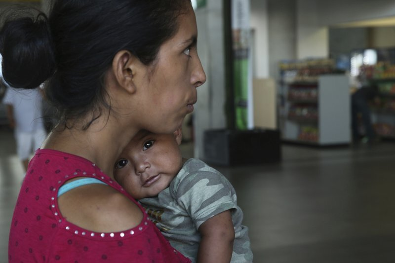 In this July 18, 2019 photo, Maria del Carmen and her 7-month-old baby stand on a sidewalk after being bused by Mexican authorities from Nuevo Laredo to Monterrey, Mexico. Maria del Carmen and her baby was returned from the U.S. side and was met by waiting Mexican immigration officials who handed documents allowing them to work and move about the country. Without further explanation they were then loaded onto chartered buses and sent to Monterrey. (AP Photo/Marco Ugarte)
