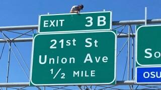 Close up shot of man on sign over I-244