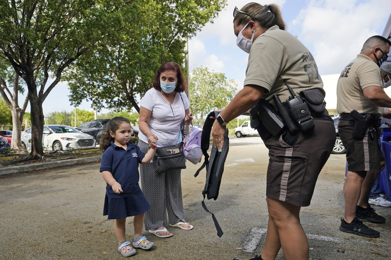 Girl receives book bag during donation drop in Miami-Dade County, July 30, 2021