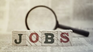 """Jobs"" on wooden block and magnifying glass on newspaper background"