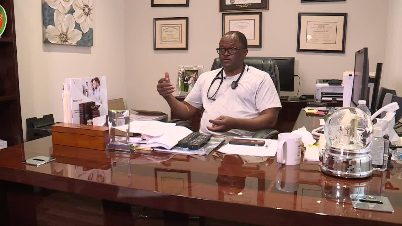 Dr. Olayemi Osiyemi sits at desk