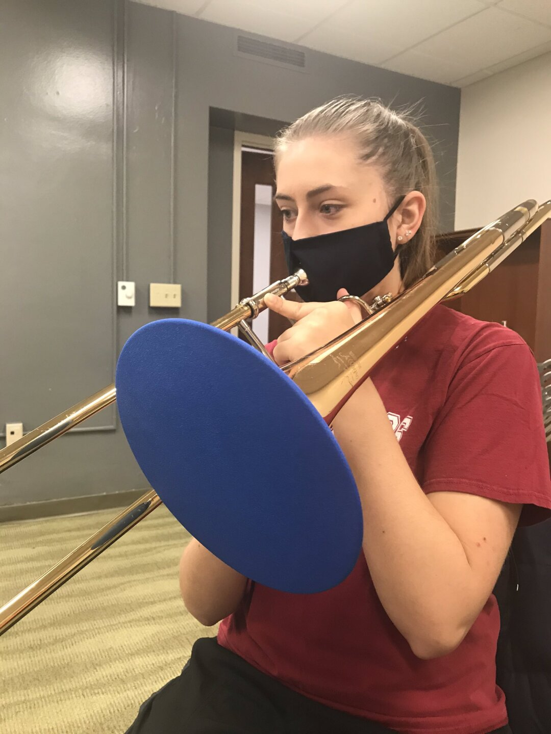 Junior Bailey Lewis plays the trombone through her special mask that allows her to rehearse with a mask on.