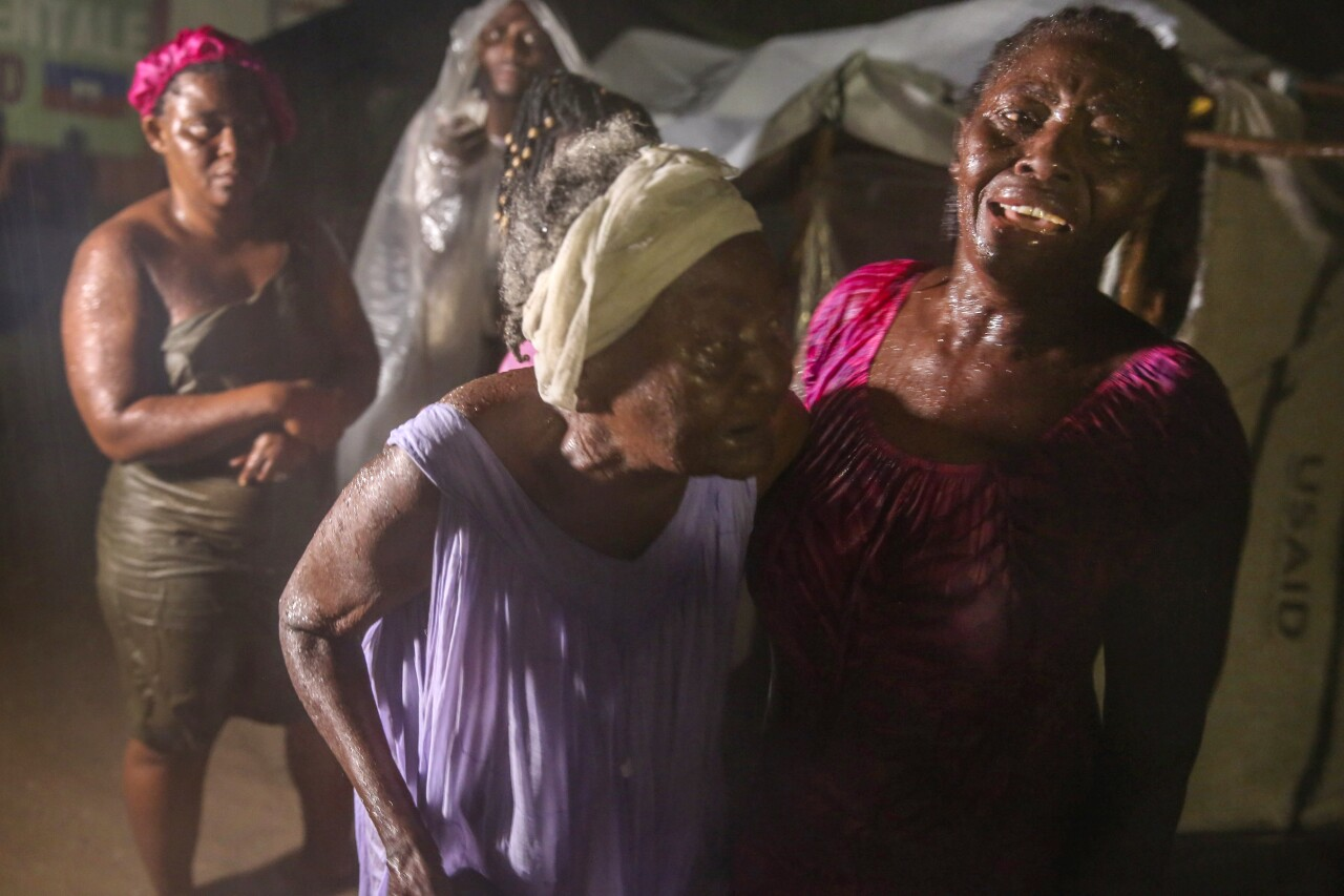 Women affected by Haiti earthquake stand in rain at refugee camp