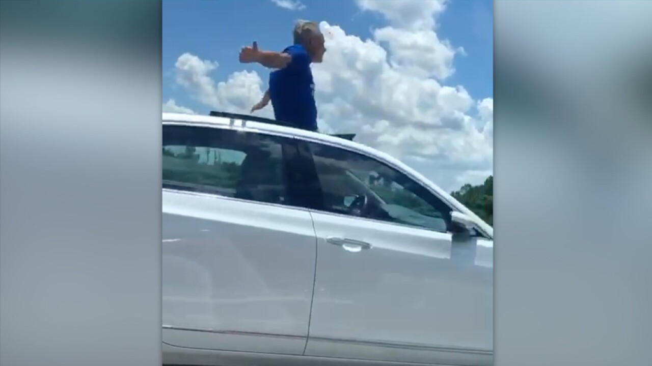 FL man hangs out sunroof.jpg