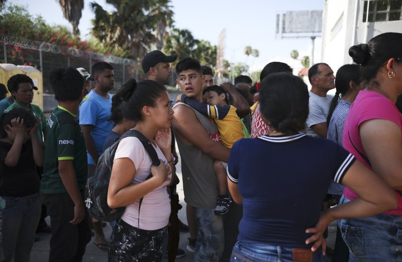 In this Aug. 1, 2019, photo, migrants line up in Matamoros, Mexico, for a meal donated by volunteers from the U.S., at the foot of the Puerta Mexico bridge that crosses to Brownsville, Texas. Turning Mexican border cities into waiting rooms for asylum seekers may be the Trump administration's most forceful response yet to a surge of migrants, many of them Central American families. (AP Photo/Emilio Espejel)