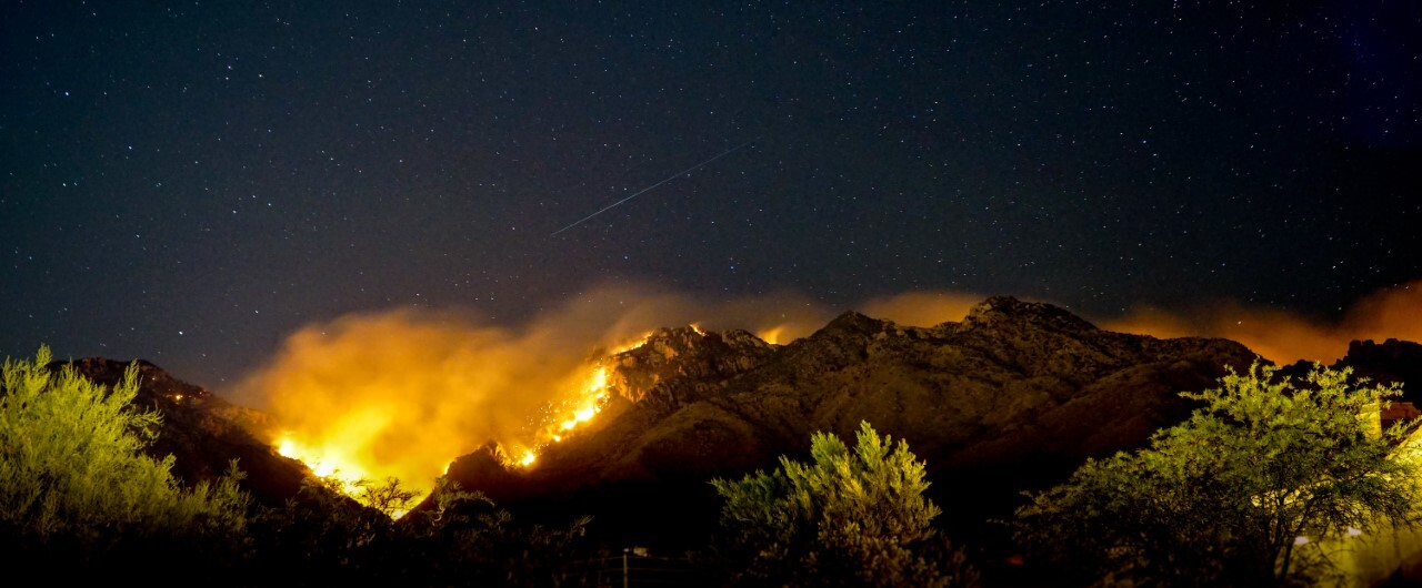 The Bighorn Fire glows steadily across the night sky in the Catalina Mountains