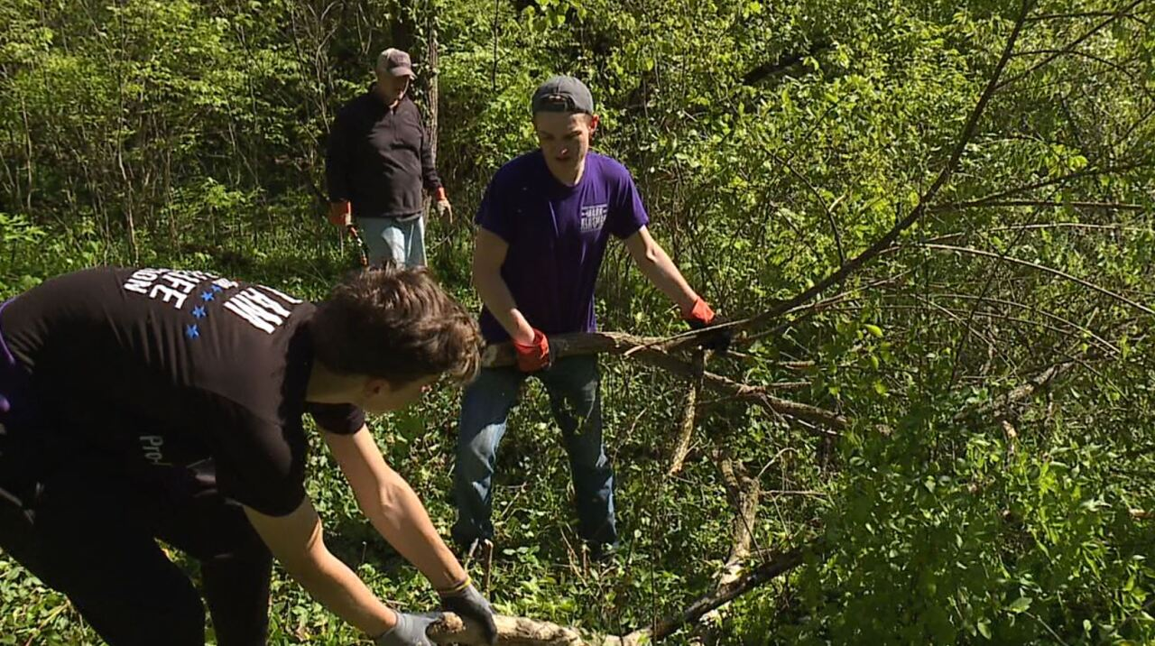 This photo shows Elder High School students helping to clear overgrown weeds and brush from Potter's Field during a volunteer event on May 1, 2021.