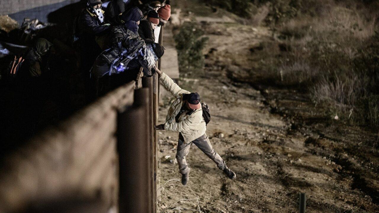 AP border migrant jumping fence night.JPG