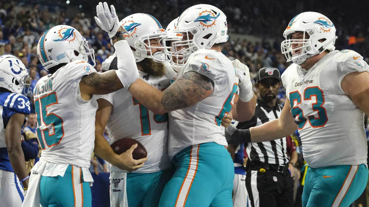 Miami Dolphins quarterback Ryan Fitzpatrick (14) is surrounded by teammates as he celebrates a touchdown against the Indianapolis Colts during the first half of an NFL football game in Indianapolis, Sunday, Nov. 10, 2019.