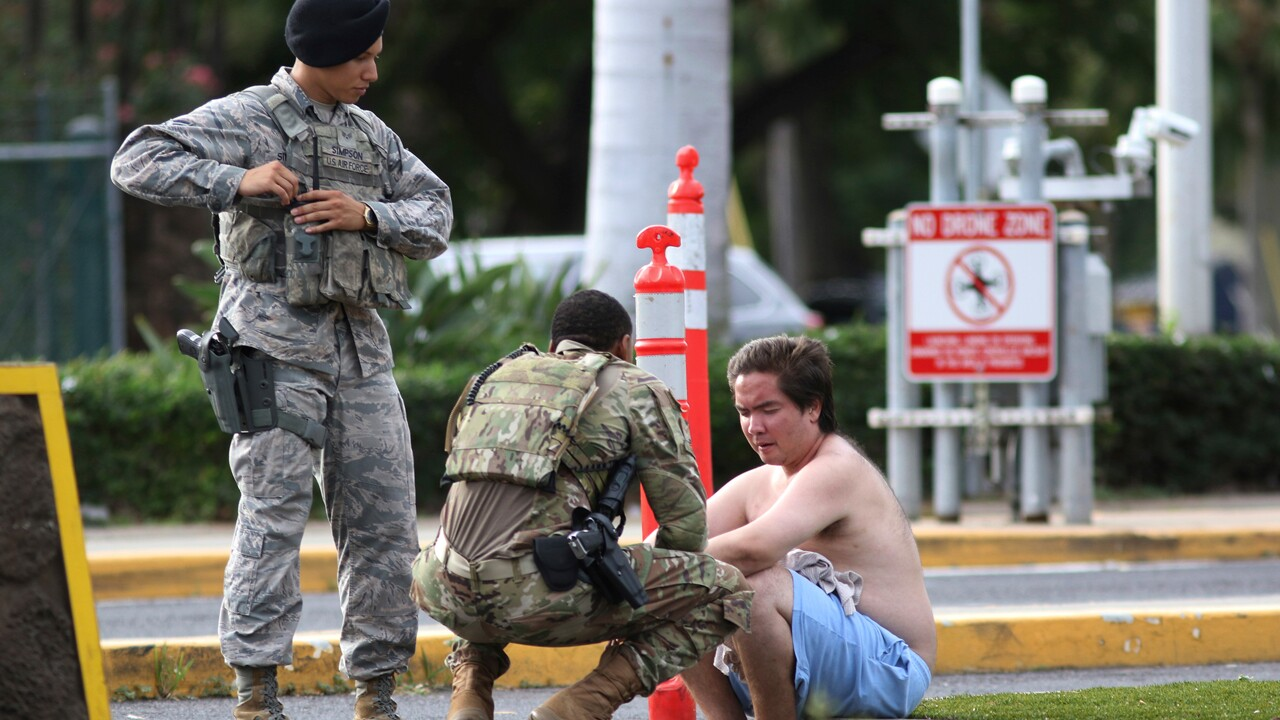 Security forces attend to an unidentified male outside the main gate at Joint Base Pearl Harbor-Hickam, Wednesday, Dec. 4, 2019, in Hawaii, following a shooting.