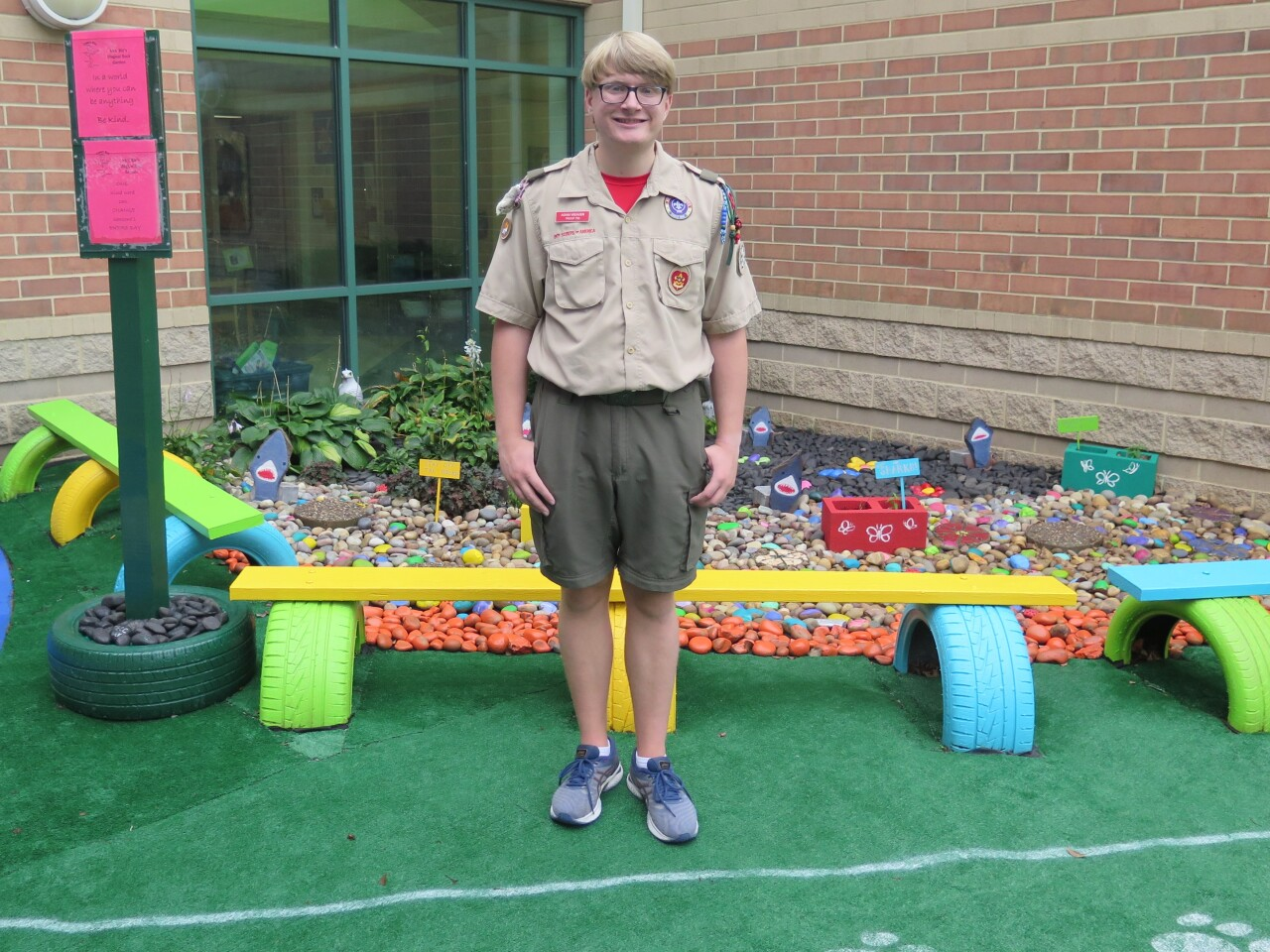 Adam Weaver poses in the MECC Moves courtyard. He has short, blond hair and glasses and is wearing his Boy Scout uniform.