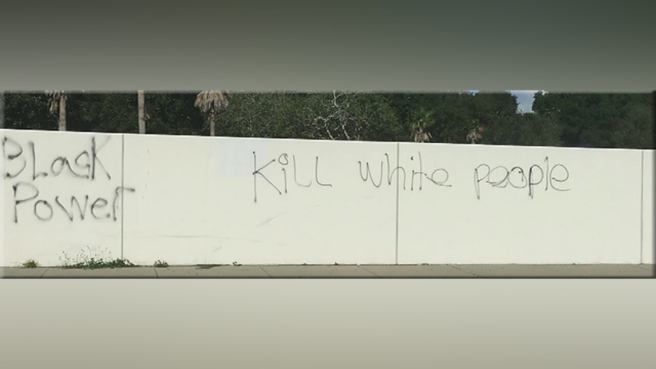 Hate graffiti spray-painted on wall and in yards
