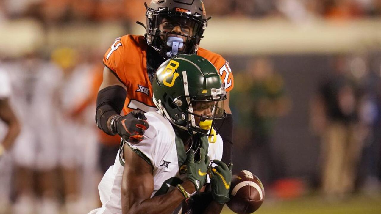 Oklahoma State cornerback Jarrick Bernard-Converse, rear, reaches in to break up a pass intended for Baylor wide receiver Tyquan Thornton in the second half of an NCAA college football game, Saturday, Oct. 2, 2021, in Stillwater, Okla. (AP Photo/Sue Ogrocki)