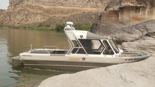 A small white boat belonging to the Twin Falls County Sheriff's Office sitting in the water near Pillar Falls.