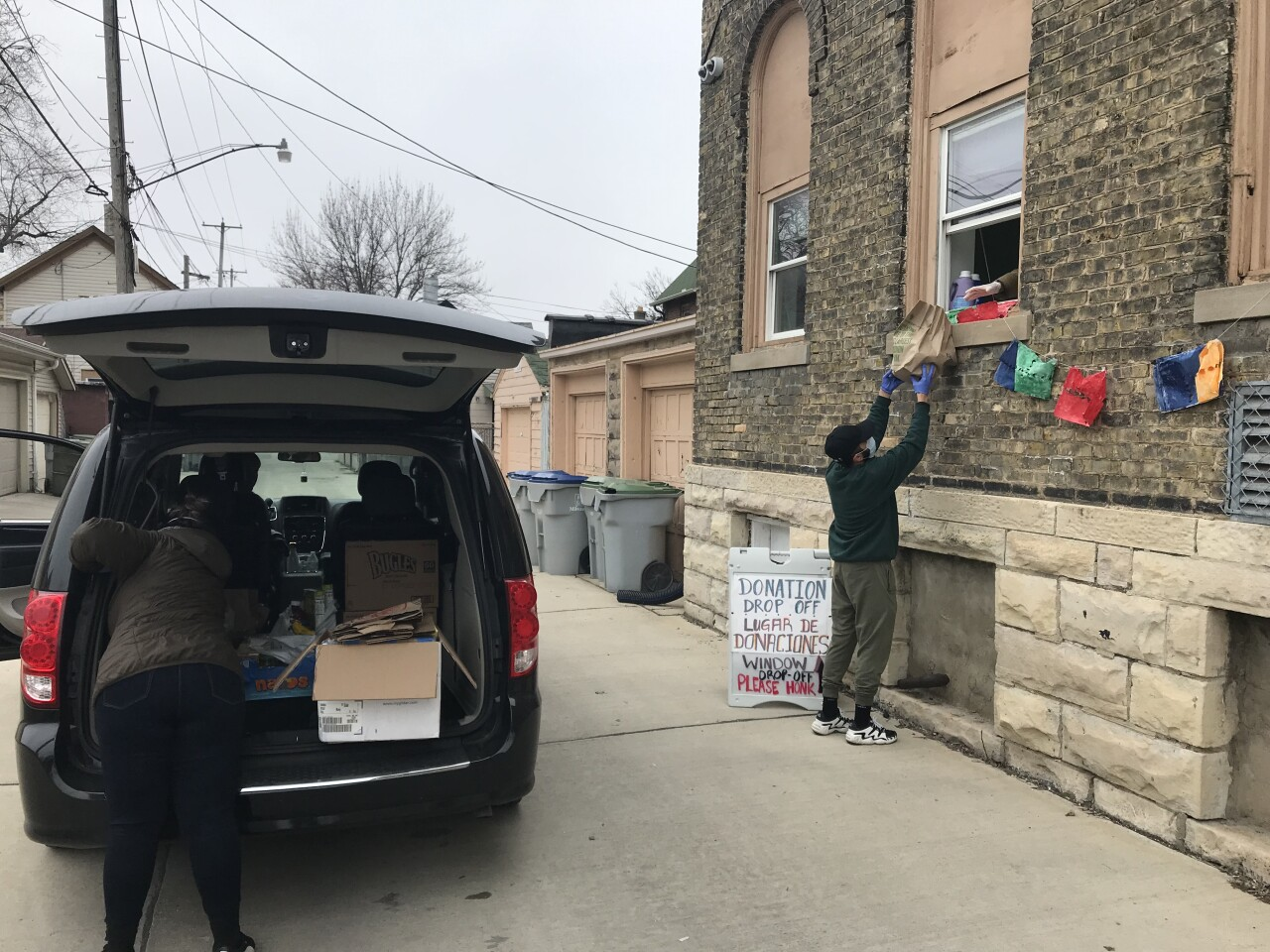 Members of Ayuda Mutua MKE help unload a car full of food donations and pass them through a window to be sorted and stored.
