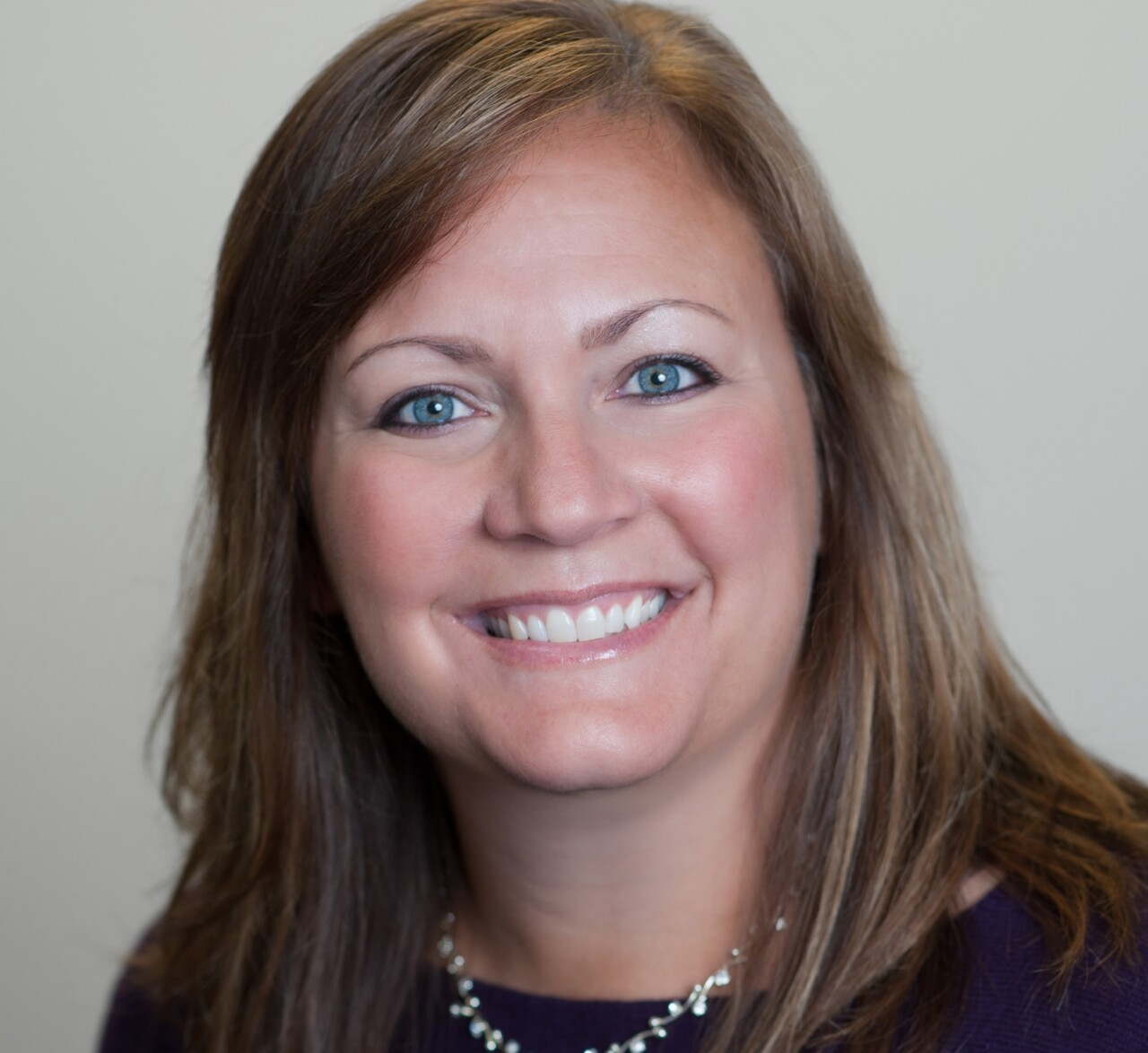 Jodi Harding is the chief operations officer at Lighthouse Youth and Family Services. In this photo, she is wearing a dark top and a necklace with white beads.