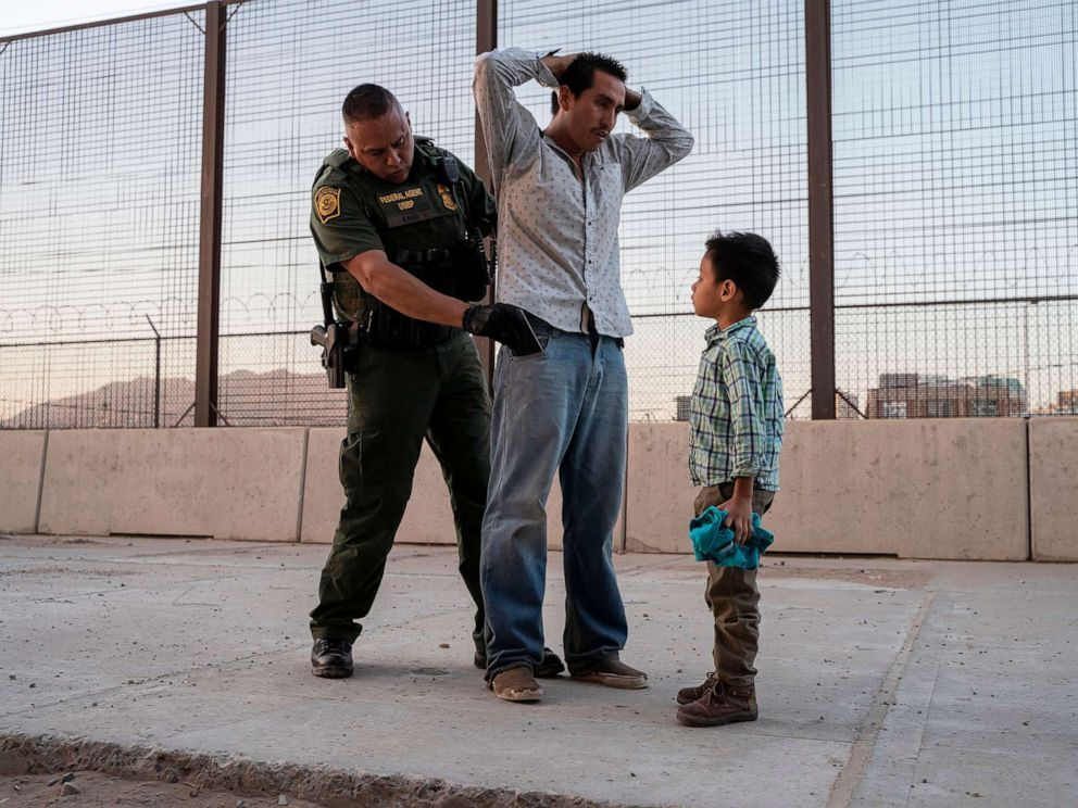 Jose, 27, with his son Jose Daniel, 6, is searched by US Customs and Border Protection Agent Frank Pino, May 16, 2019, in El Paso, Texas (Paul Ratje/AFP/Getty Images).