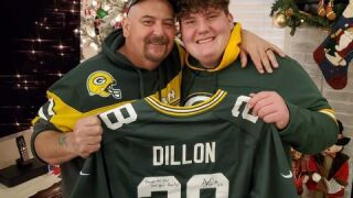 Brian and David Zloch hold signed AJ Dillon jersey
